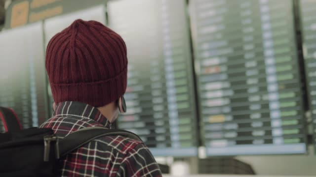 vídeos de stock, filmes e b-roll de homem hipster olhando para placa de partida do aeroporto - homens jovens