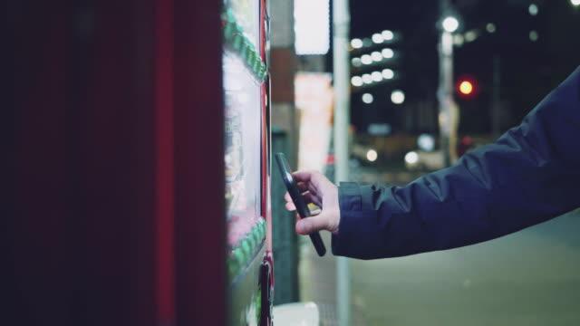 vídeos y material grabado en eventos de stock de hombre hipster pagando con teléfono inteligente a la máquina expendedora. - pago por móvil