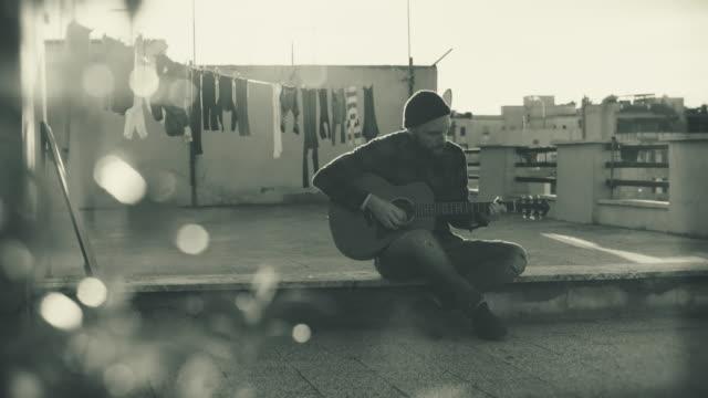 Hombre hipster tocando la guitarra acústica en la terraza: vídeo monocromo