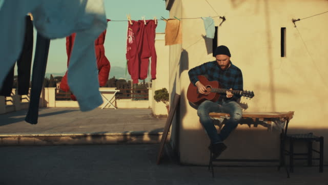hipster man playing acoustic guitar on the terrace - guitar stock videos & royalty-free footage