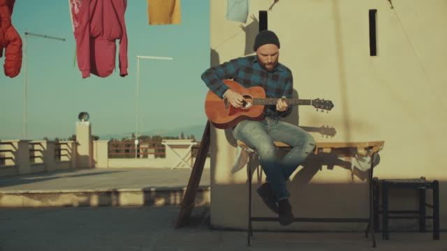 Hipster Mann spielen Akustikgitarre auf der Terrasse