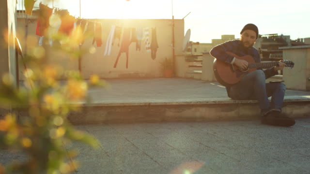 hipster man playing acoustic guitar on the terrace - balcony stock videos & royalty-free footage