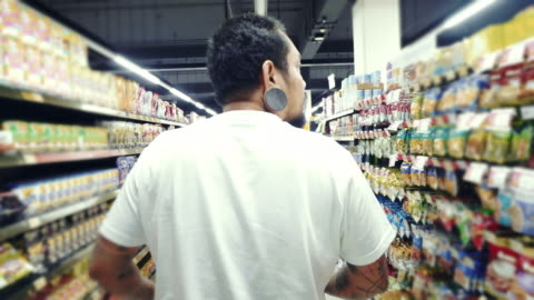 hipster man shopping i en stormarknad - etikett bildbanksvideor och videomaterial från bakom kulisserna
