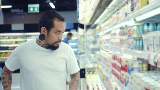 stockvideo's en b-roll-footage met hipster man winkelen in een supermarkt - dairy product
