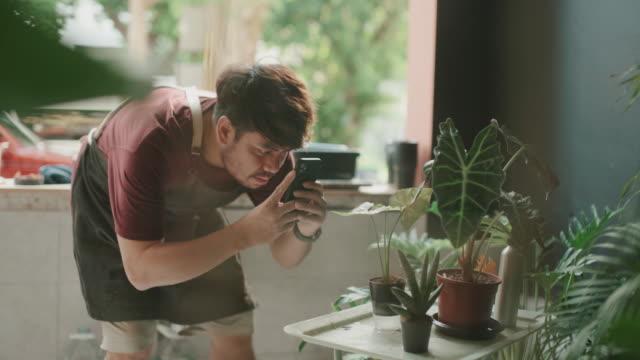 vídeos de stock e filmes b-roll de hipster man take photo to the plants and checking at home - colocar planta em vaso