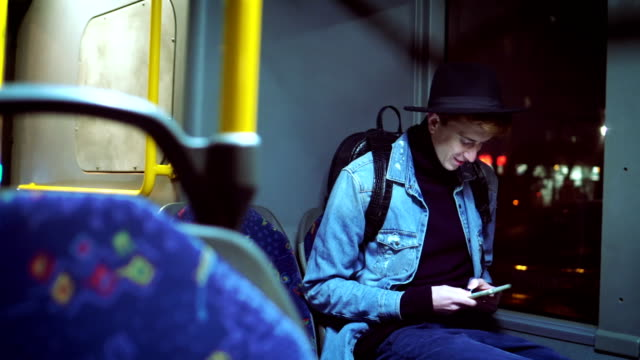 vídeos de stock e filmes b-roll de hipster man texts messages in bus - veículo terrestre comercial