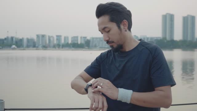 hipster mann verwendung von smart watch und handy - menschliche gliedmaßen stock-videos und b-roll-filmmaterial