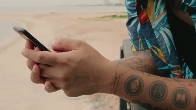 Hipster man using his smart phone at the beach