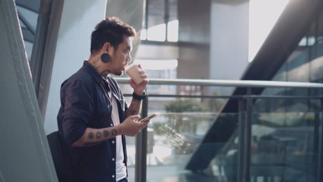 hipster man using mobile phone on rooftop at sunset - piercing video stock e b–roll