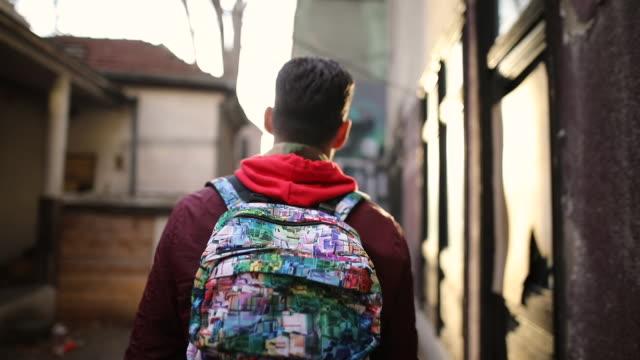 街を歩くカラフルなバックパックを持つヒップスターの男 - 人の背中点の映像素材/bロール