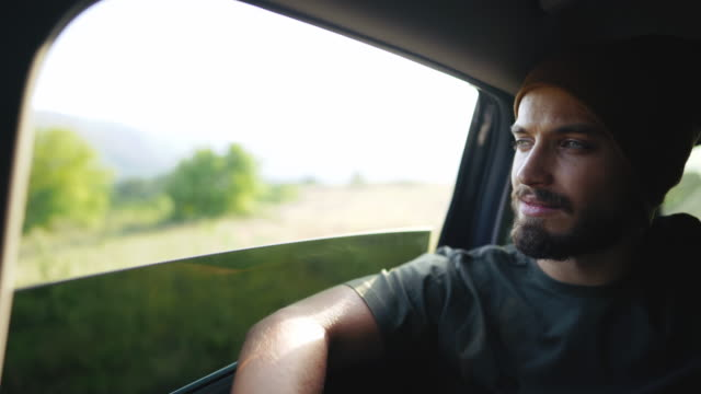 hipster man with knit cap driving on the back seat in car - car interior stock videos & royalty-free footage
