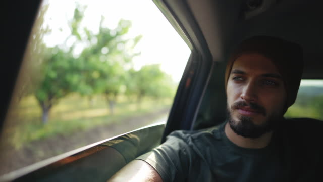hipster man with knit cap driving on the back seat in car - peluria del viso video stock e b–roll
