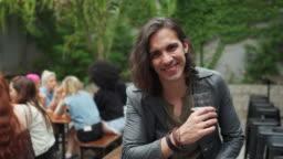 Hipster man with long hair enjoying beer in bar