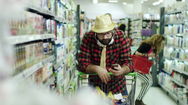 Hipster men using smartphone in supermarket
