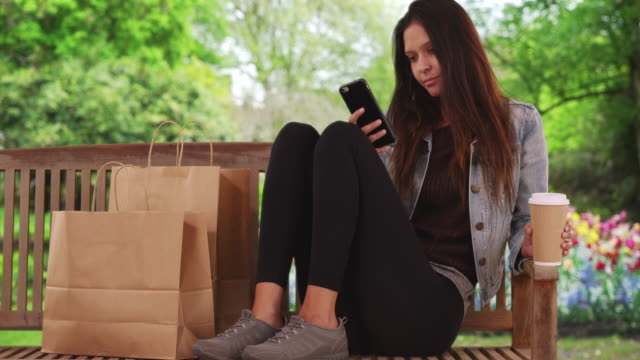 hipster millennial female sits on park bench by tulip garden texting - shopping bag stock videos and b-roll footage