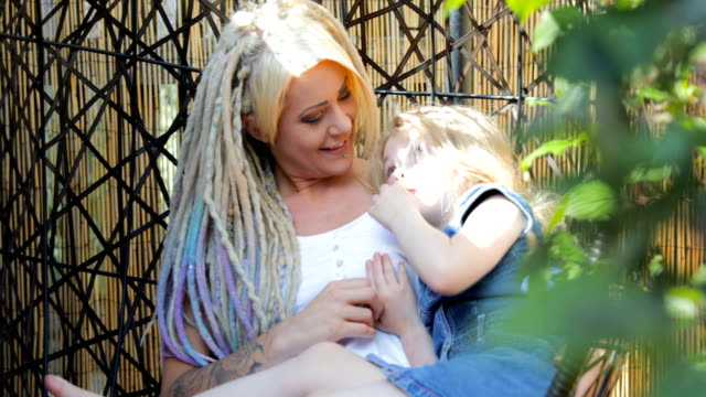 Hipster Mother Sitting in the Back Yard Swing with Daughter