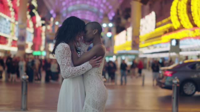 slo mo. hipster newlywed brides dance in their wedding dresses in front of a crowd of people on fremont street in las vegas - lesbe lesben stock-videos und b-roll-filmmaterial