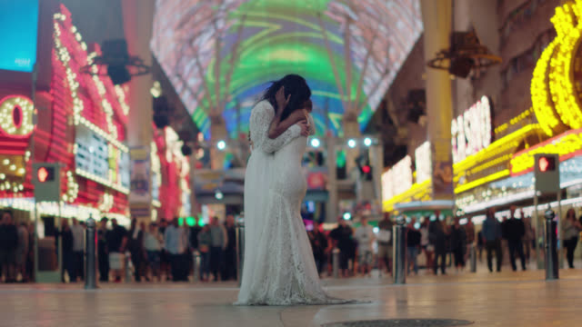 hipster newlywed brides dance in their wedding dresses in front of a crowd of people on fremont street in las vegas - lesbe lesben stock-videos und b-roll-filmmaterial