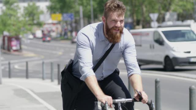 vídeos de stock, filmes e b-roll de hipster é andar de bicicleta depois de usar um smartphone na cidade - bicicleta