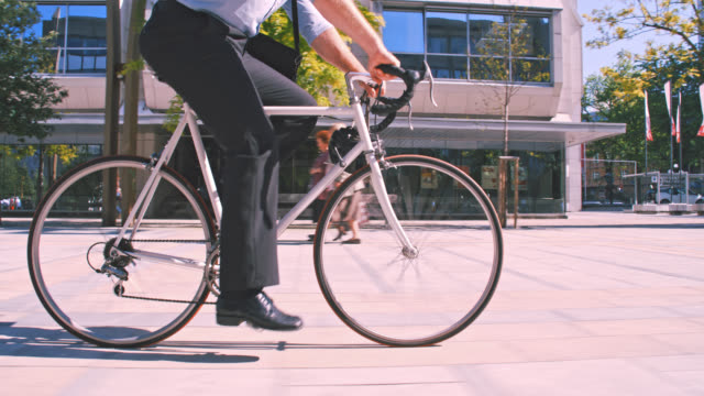 slo mo hipster in sella alla sua bici mentre va al lavoro - moving past video stock e b–roll