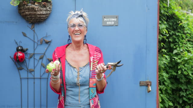 hipster senior woman outside her potting shed - day in the life stock videos & royalty-free footage