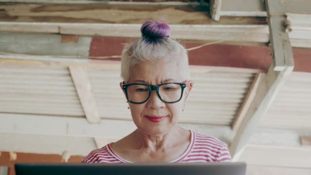 hipster senior woman working with computer at home stock vdo - south east asia stock videos & royalty-free footage