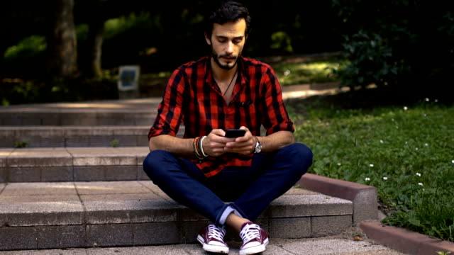 hipster sitting on steps in park - jeans stock videos & royalty-free footage