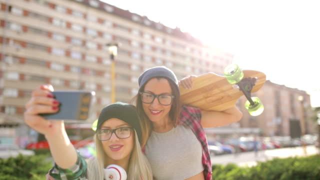 vídeos de stock, filmes e b-roll de hipster de skate meninas fazendo selfie - woolly hat