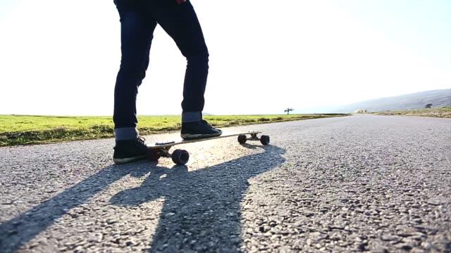 Hipster skateboarder skating on mountain road