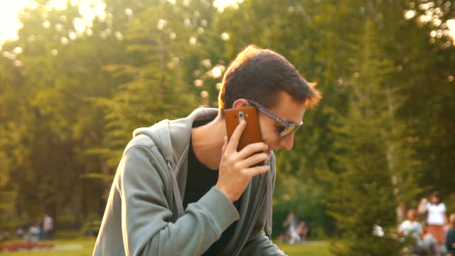 hipster talking on the phone in the park - hanging up stock videos and b-roll footage