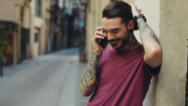 stockvideo's en b-roll-footage met hipster getatoeëerd man in barcelona met mobiele telefoon - tatoeage