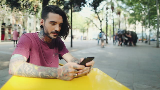 hipster tattooed man in barcelona with mobile phone - tattoo stock videos & royalty-free footage