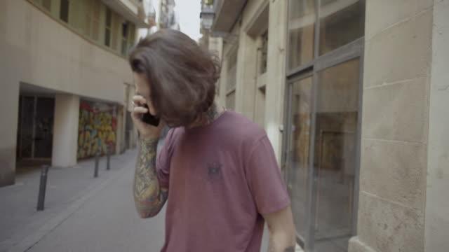 携帯電話を持つバルセロナのヒップ入れ墨男 - ゴシック地区点の映像素材/bロール