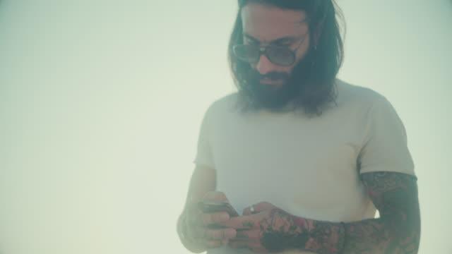 Hipster tätowierte Rebellen Kerl mit Handy