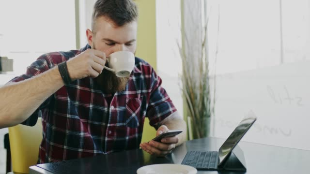 ds hipster using a smartphone while drinking cappuccino at the table - plaid shirt stock videos & royalty-free footage
