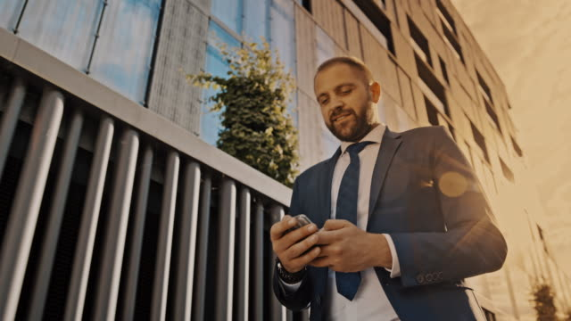 slo mo hipster using a smartphone while walking along an office building at sunset - solo uomini di età media video stock e b–roll