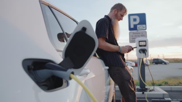 vídeos y material grabado en eventos de stock de slo mo hipster usando su teléfono inteligente mientras su coche está siendo cargado en la estación de carga - aparcamiento