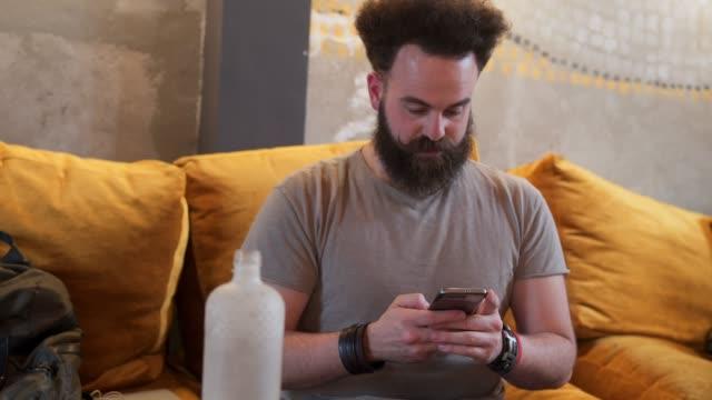vídeos de stock e filmes b-roll de hipster using mobile phone in coffee shop - masculinidade moderna