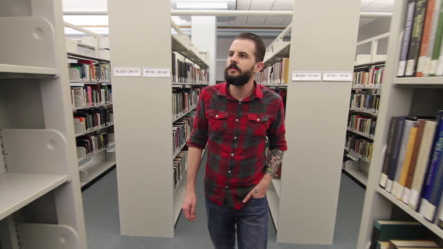 Hipster Walking Through the Library