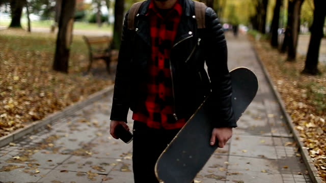 Hipster with skateboard walking