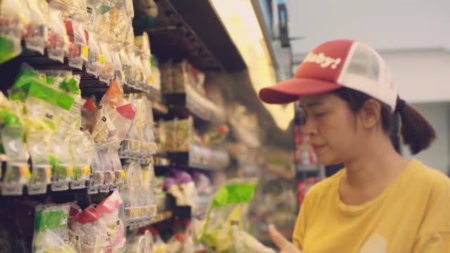 hipster woman buying food in supermarket. - vegetarian food stock videos & royalty-free footage
