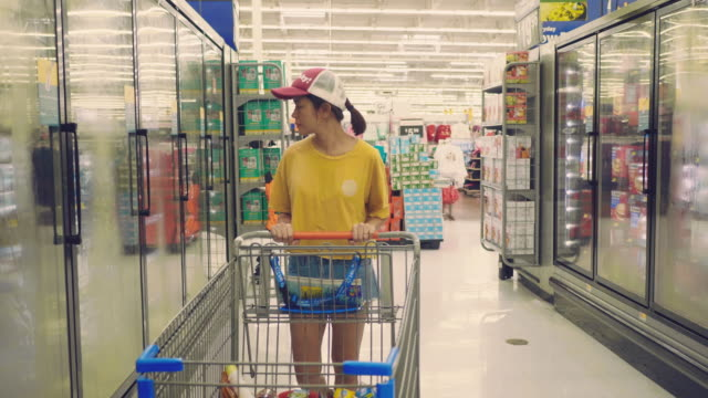 Hipster woman buying some frozen food at refrigerated section in local supermarket.