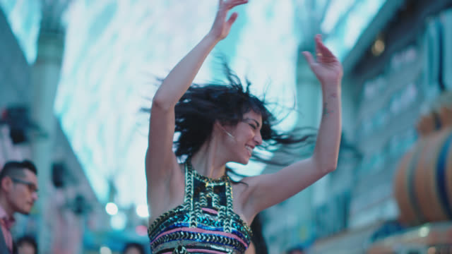 slo mo. hipster woman dances with a group of friends on fremont street in las vegas - junges paar stock-videos und b-roll-filmmaterial
