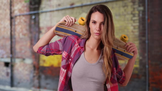 vídeos y material grabado en eventos de stock de hipster woman holding skateboard on her shoulders - personas bellas