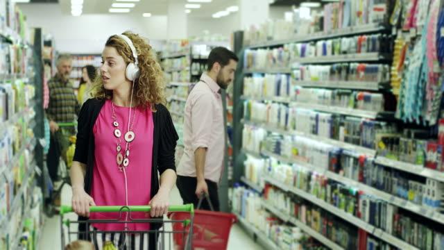vídeos y material grabado en eventos de stock de mujer hipster escuchando música en auriculares y la compra de productos alimenticios en supermercado - super slow motion