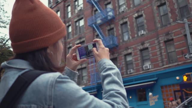 vidéos et rushes de touristique de femme hipster coup d'oeil à la photo sur smartphone - photographe