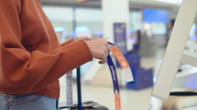Hipster woman using self check-in machine in the airport