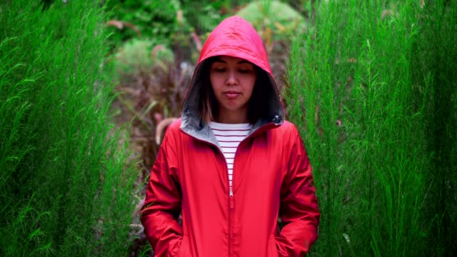 hipster woman wearing a red hood standing in nature - cappuccio video stock e b–roll