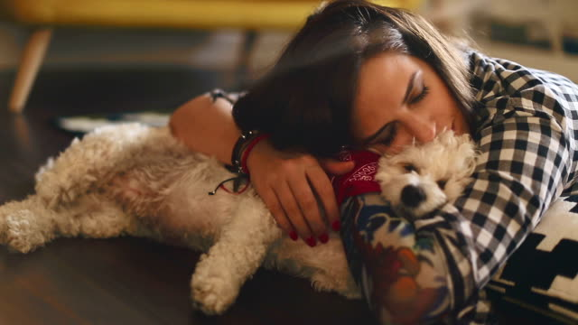 Hipster woman with tattoo playing with her puppy while lying on the floor