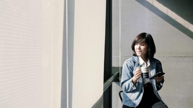 コーヒーを飲みながら携帯電話で働くヒップスターの女性 - ショートヘア種の猫点の映像素材/bロール